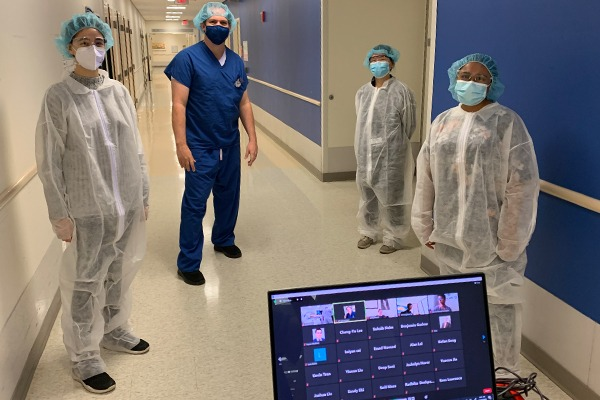 Three students and one professor are wearing scrubs in the hall of a hospital with a computer showing more students on a Zoom meeting.