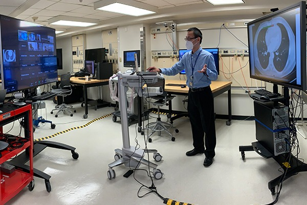 A professor is in a lab teaching virtually to a screen of students on Zoom.