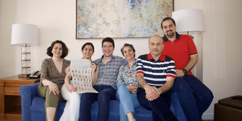 Azhir and family gather on the couch for a photo.