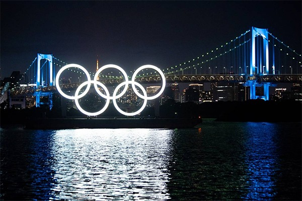 The Olympic rings are lit up in front of a bridge.