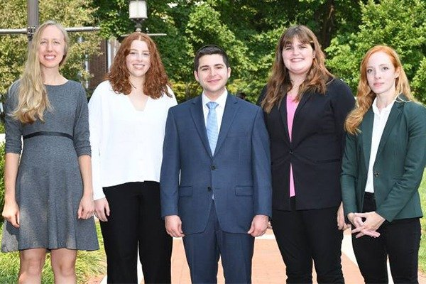 Four women and one man stand together for a photo.
