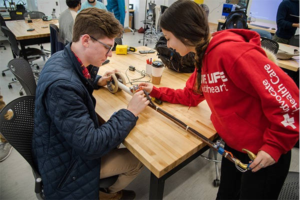 Two students are at a table working on a design project.